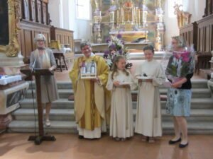 Kirchgemeindepräsidentin überreicht der Pfarrfamilie Abschiedsgeschenke.