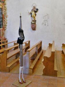 Skulptur vor den Kirchenbänken