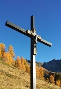 Kreuz mit Jesus-Figur in den walliser Alpen