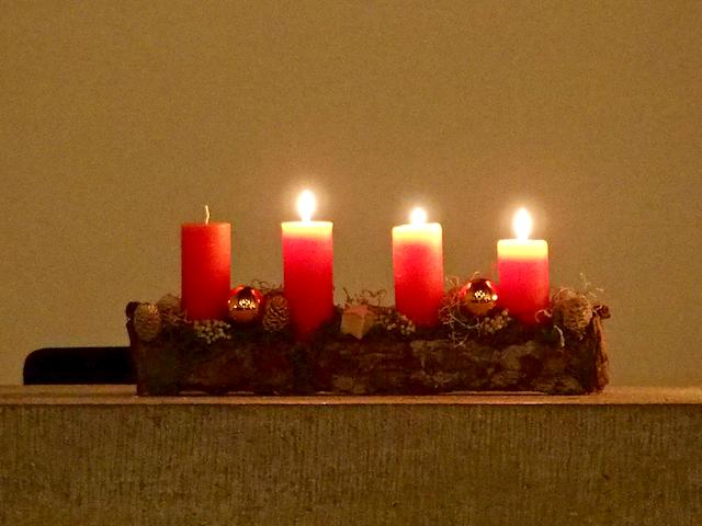 Drei brennende Kerzen auf einem Altar.